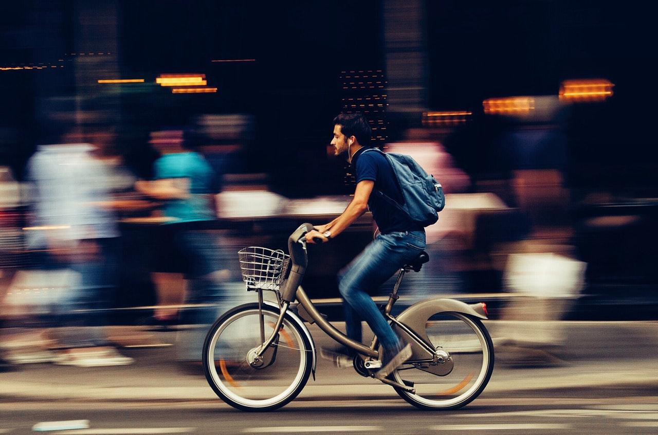 vyras važiuoja dviračiu gatvėje pro daug žmonių