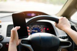 žmogus laiko telefoną ir automobilio vairą