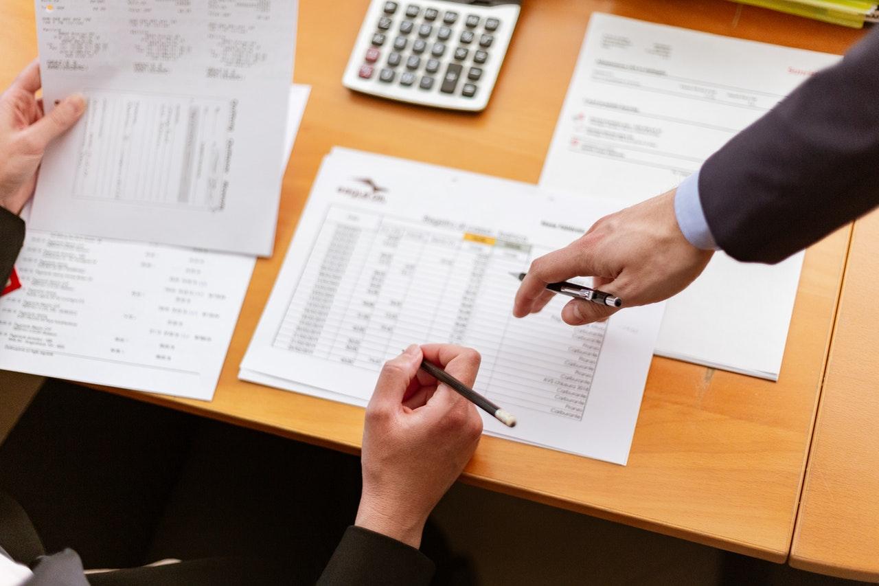 du žmonės pasidėję dokumentus ant stalo skaičiuoja